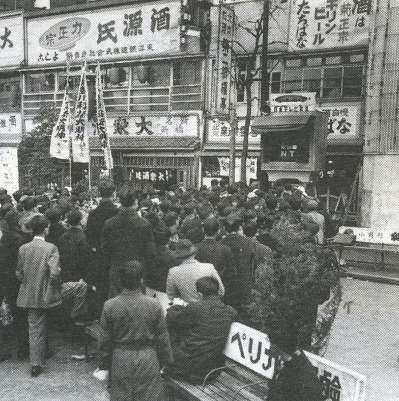 新橋駅前で街頭テレビをモニターする内藤(左端の後ろ姿)