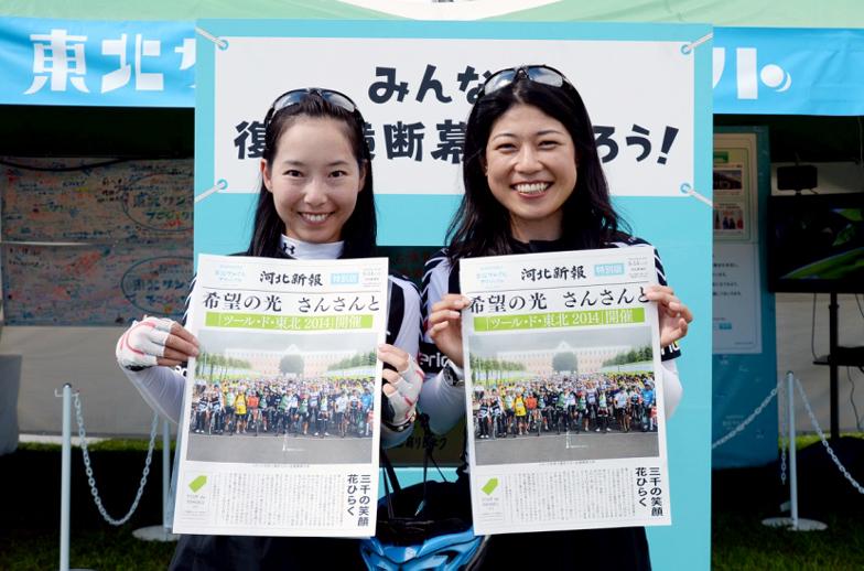 自身が写った河北新報特別版を受け取り、笑顔を見せる参加者
