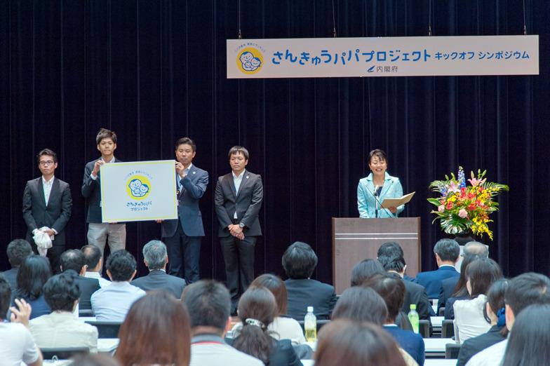 壇上では実際に休暇を取った内閣府職員4人がシンボルマークを紹介した。