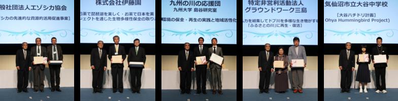 岡田理事長から表彰楯と副賞、記念品を受け取った各団体代表者ら