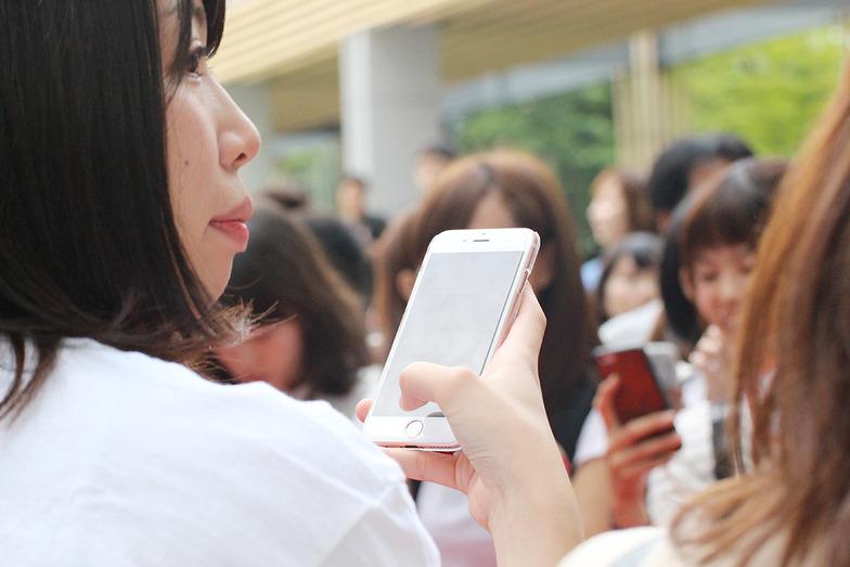スマートフォン片手に、イベント会場で撮影やツイートをするファンのみなさん