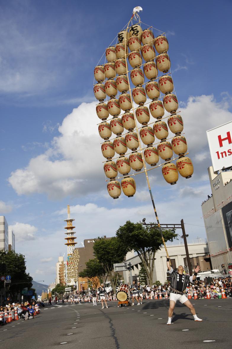 晴れ渡った空に向かい、巨大な竿燈を自在に操る妙技で魅せた「秋田竿燈まつり」