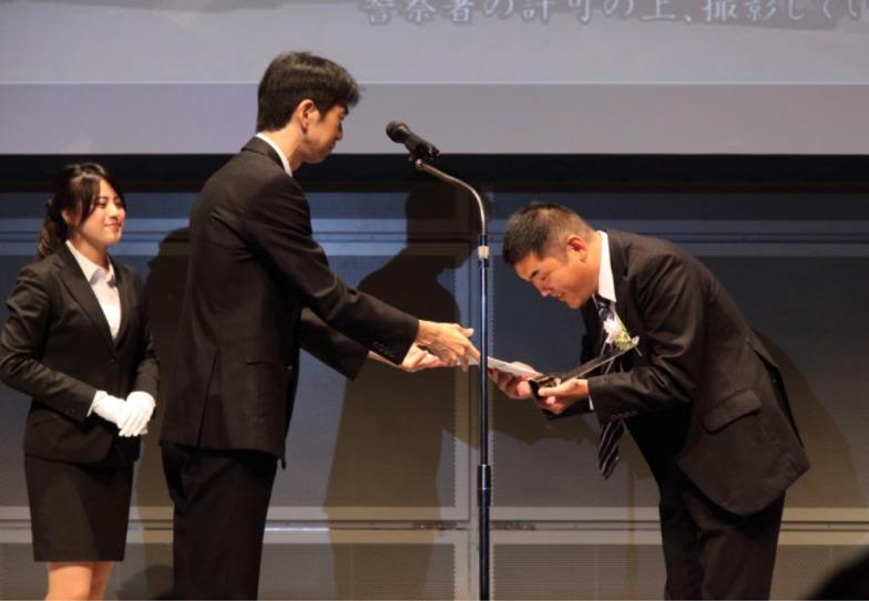 総務省・飯村博之地域放送推進室長(左)と グランプリ受賞の京丹波町ケーブルテレビ 西村美貴氏