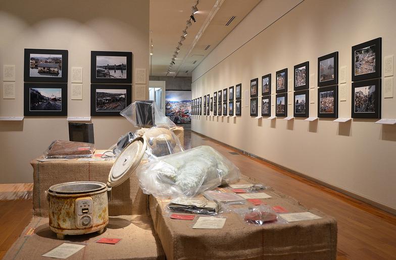 「東日本大震災の記録と津波の災害史」常設展示会場。被災現場写真203点、被災物155点、歴史資料など137点を展示。泥のついた炊飯器や携帯電話などの品々が、かつての持ち主の暮らしを伝えている。