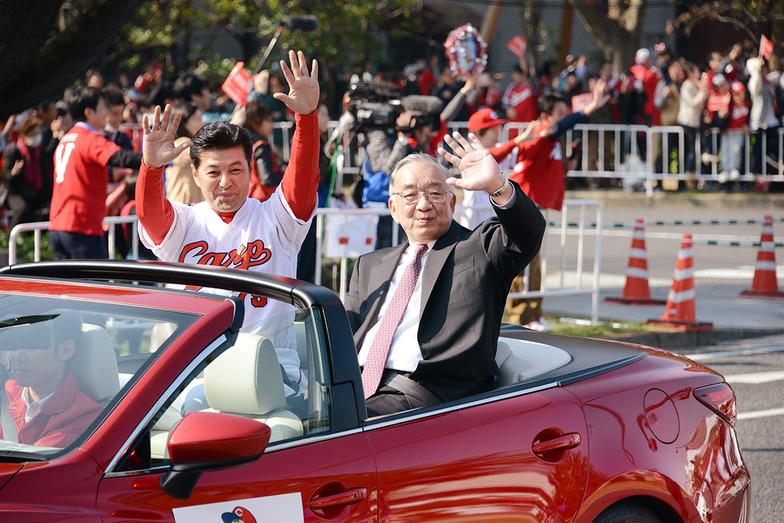 手を振る緒方孝市監督(左)と松田元オーナー(右)