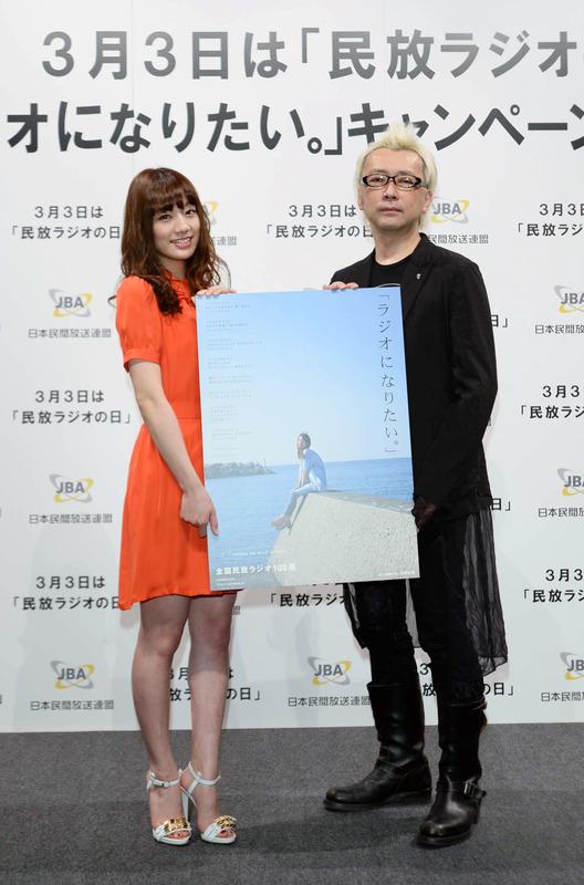 ポスターを手に佐藤さん(左)と箭内プロデューサー