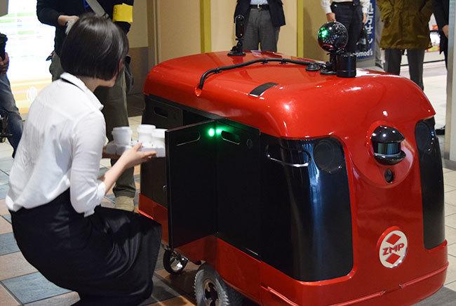 カフェ店員がCarriRo Deriveryにコーヒーを搭載。右上に光る球体がコミュニケーション担当のTiCAだ。