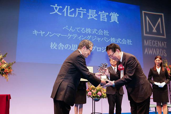 文化庁の宮田亮平長官が、文化庁長官賞のぺんてる・キヤノンマーケティングジャパンを表彰