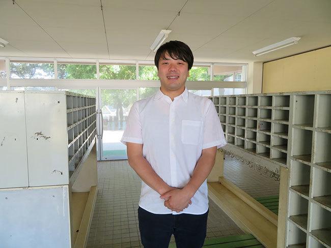 北日本新聞社の石田氏。今もきれいな姿で残る下駄箱の前で撮影