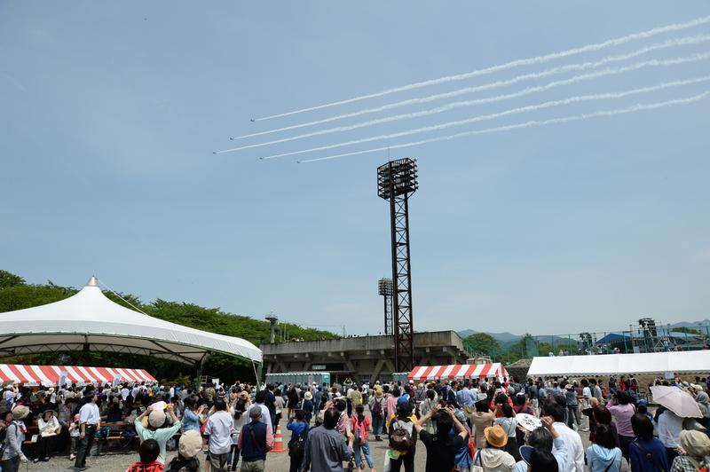ブルーインパルスもアクロバット飛行で盛り上げに一役。 カメラに収めようと見上げる来場者ら