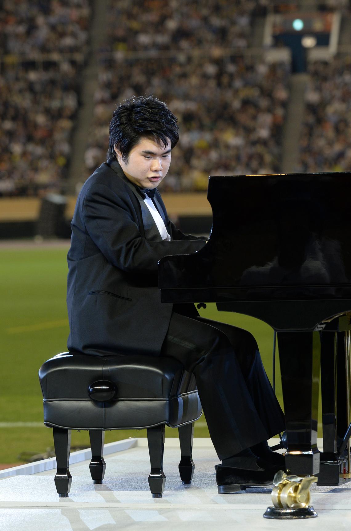 競技場にグランドピアノが運び込まれ、ピアニストの辻井伸行さんが黒いタキシード姿で登場