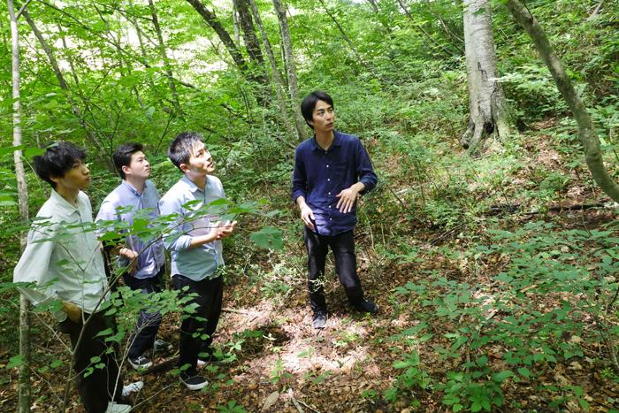 矢野建築設計事務所のメンバーを森に案内するヒダクマの松本氏(右)