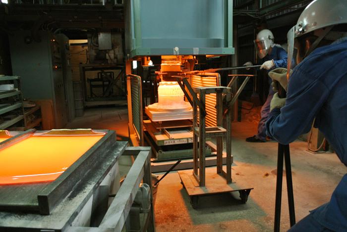 ガラス溶解炉と溶融したガラスの成型作業